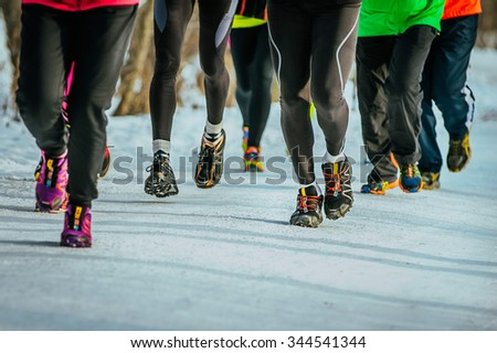 closeup feet group athletes running snowy path in woods - stock photo