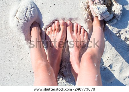 Closeup feet of mother and kid on white sand beach - stock photo