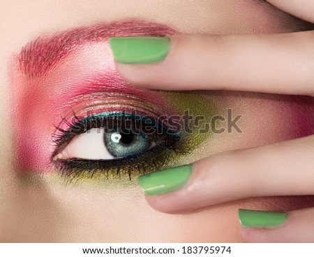 Closeup female eye with beautiful fashion bright makeup and manicured hand with green nail polish - stock photo