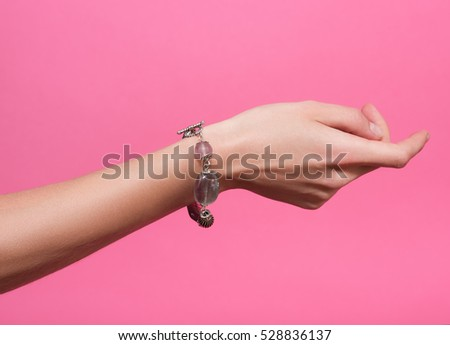 Closeup female hand with a bracelet on your wrist. Handmade jewelry and accessories. Isolated on pink background