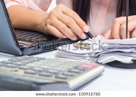 Closeup female hand working with bills on the desk - stock photo