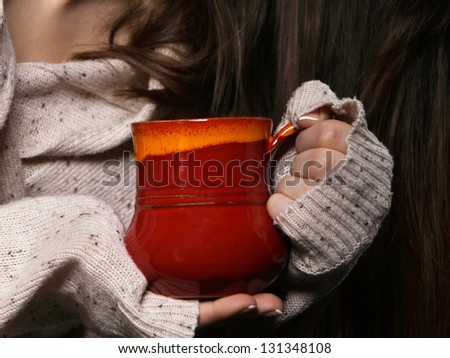 Closeup female hands holding a nice red cup of hot drink