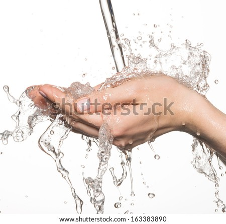 Closeup female hands under the stream of splashing water - skin care concept - stock photo
