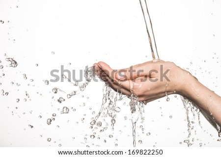 Closeup female hands under the stream of splashing water - skin care concept - stock photo