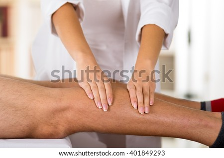 Closeup female physio therapist hands working on male patients legs, blurry clinic background