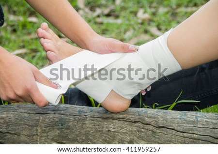 Closeup females injured ankle, getting bandage compression wrap
