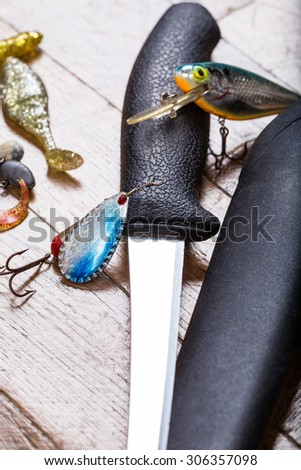 closeup fishing baits and filet knife on white wooden background - stock photo