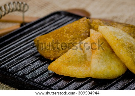 Closeup five empanadas lying in fan formation on black metal grill tablet. - stock photo