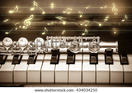 Closeup Flute on the keyboard of piano with music melody, musical instrument, vintage tone - stock photo