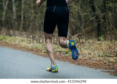 closeup foot of young runner men running along road in forest during marathon