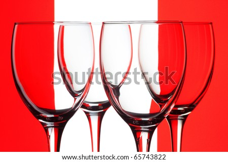 Closeup four empty wine glass on a red and white background