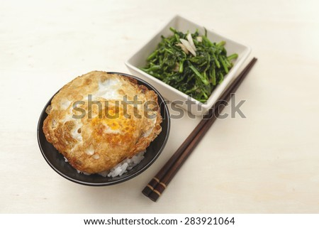 Closeup Fried vegetable and rice with crispy fried egg with space on wood table background - stock photo