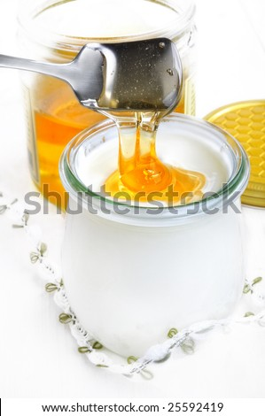 closeup from pouring honey into a glass with yoghurt - stock photo
