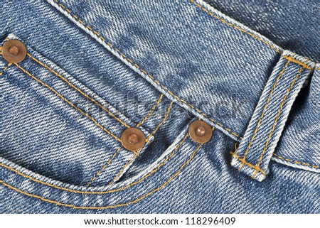 Closeup from the pocket of an old and worn blue jeans