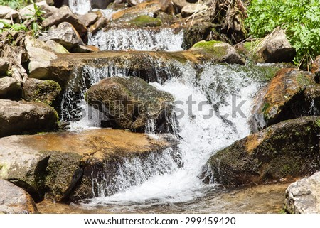 closeup frozen stream rapid waters of mountain river strong - stock photo