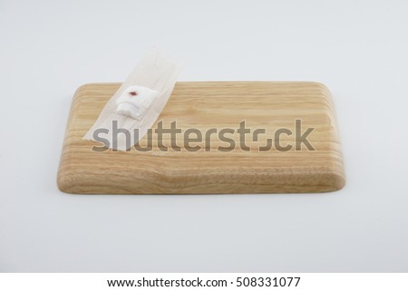 Closeup gauze pad that has been used after donating blood is placed on a wooden floor with a white background.