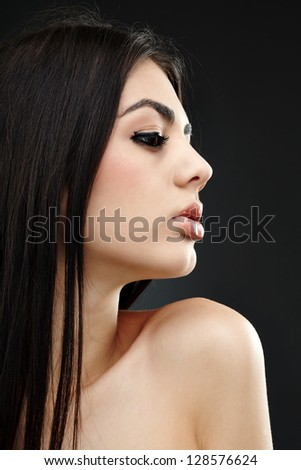 Closeup glamour pose of beautiful brunette woman over gray background - stock photo