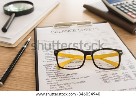 closeup glasses place on the balance sheet on desk's auditor. - stock photo