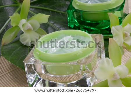 Closeup gorgeous blooming green colored Cattleyas orchid flowers and jars of cosmetics cream.