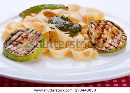 Closeup grilled zucchini round with noodles