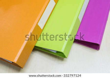 Closeup group of colorful document file on wood desk background - stock photo