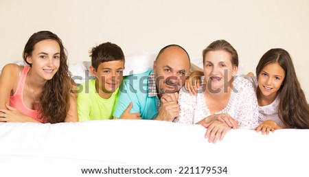 Closeup group portrait happy family, mother, father, children posing under duvet, blanket looking at camera on the bed at home, isolated room background. Positive emotions, face expressions, feelings - stock photo