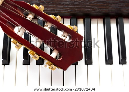 Closeup guitar neck on piano keys. Abstract and art background. Top view. - stock photo
