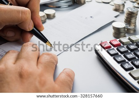 Closeup hand calculated bill on the desk - stock photo