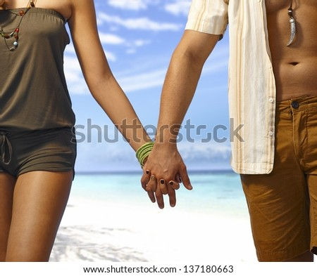 Closeup hand in hand, young couple walking on the beach at summertime. Only body part.