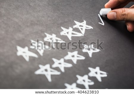 Closeup hand mark five stars rating on chalkboard - stock photo