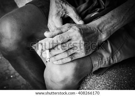 Closeup hand old man hold smoke,black and white tone - stock photo