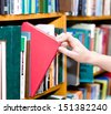 closeup hand selecting book from a bookshelf - stock photo