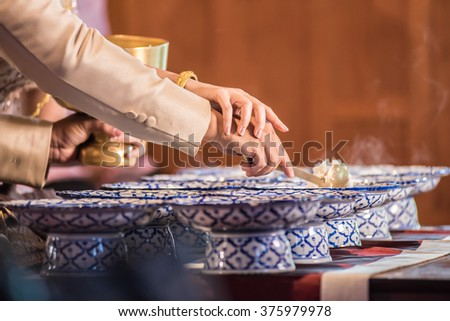 Closeup hands alms food to a Buddhist monk in traditional Thai wedding ceremony - stock photo