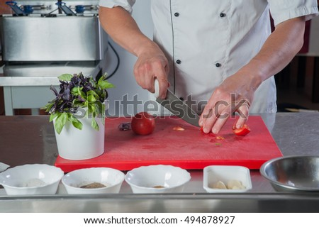 closeup hands of chef cuts a tomato with a knife on the kitchen blackboard