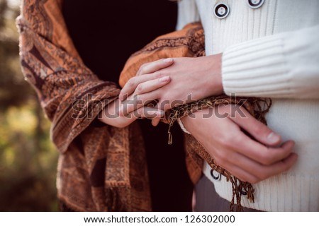 closeup hands of happy young couple in love outdoor in autumn - stock photo