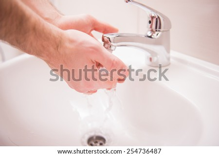 Closeup hands of man is washing hands under running water.