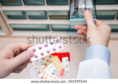 Closeup hands of pharmacist man choosing medicines at pharmacy. Drug store.Medical image.  - stock photo