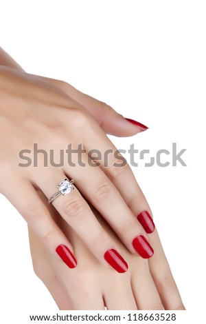 closeup hands of young woman with red manicure polished nails wearing an expensive engagement ring with a diamond on white background - stock photo