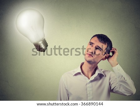 Closeup handsome concerned man thinks looking up at bright light bulb isolated on gray wall background. Idea, business, education and people concept. Human face expression - stock photo