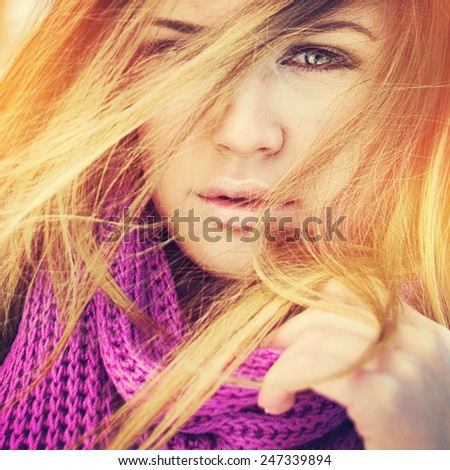 Closeup head shot of beautiful young green eyed blonde woman with purple scarf and flying hair posing. Square format, filter, instagram look, vibrant warm colors. - stock photo