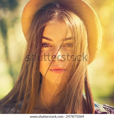 Closeup head shot of beautiful young green eyed brunette woman with hat, long flying hair posing looking at camera. Square format, filter, instagram look, vibrant warm colors. - stock photo
