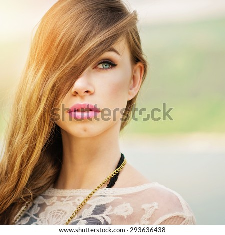 Closeup head shot of gorgeous young blonde blue eyed woman at the beach. Beautiful girl with long hair wearing makeup and sheer beige dress. Square format, retouched, vibrant colors. - stock photo