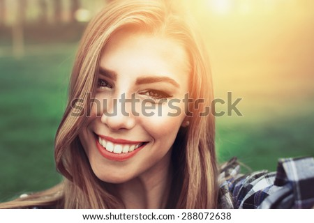 Closeup head shot selfie of beautiful young Caucasian blonde woman smiling. Happy pretty teenage girl taking a selfie in park on sunny summer day. Retouched, back light, horizontal, vibrant colors. - stock photo