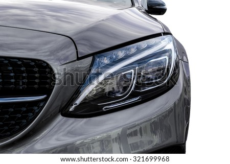 Closeup headlights of grey car and Car exterior detail with White back. Closeup headlights of car. Modern luxury car close-up banner background. Concept of expensive, sports auto Closeup headlights - stock photo