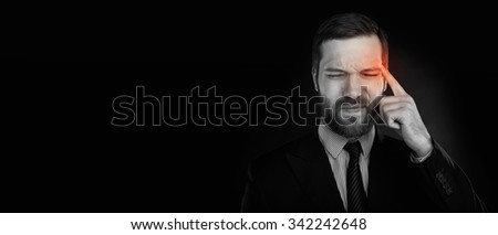 Closeup headshot businessman suffering from headache hand on head with red colored inflamed area looking down isolated on black wall background. Human face expression. Health problems issues - stock photo