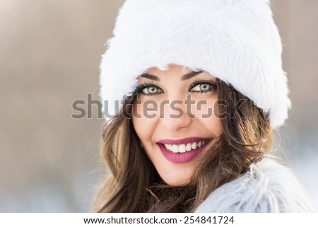 Closeup headshot of beautiful green eyed woman in winter. Young brunette woman with makeup and white fuzzy hat. Natural light, retouched, selective focus, shallow depth of field, horizontal, copyspace - stock photo