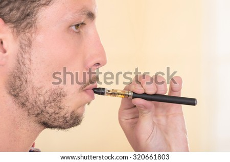 Closeup headshot of man smoking on electronic cigarette from profile angle.