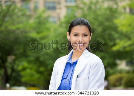 Closeup headshot portrait of friendly, cheerful, smiling confident female, healthcare professional with lab coat. isolated outdoors outside green trees background. Patient visit. - stock photo