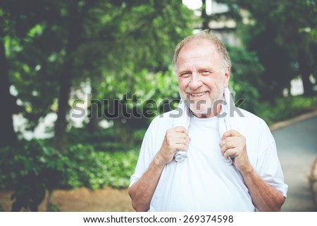 Closeup headshot portrait of happy  senior mature man, grasping towel around neck, isolated green trees foliage background. Positive human emotions, facial expressions. Retro faded vintage look - stock photo