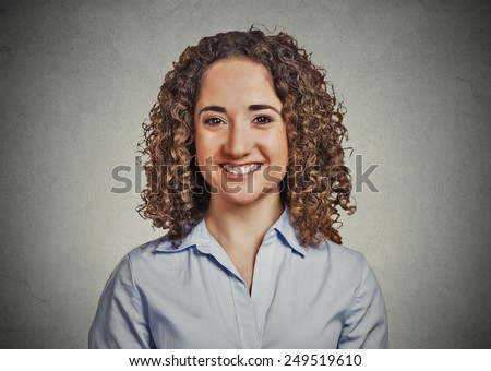 Closeup headshot portrait, young beautiful business woman with curly hair in blue shirt smiling isolated on grey wall background. Positive human emotion facial expression - stock photo
